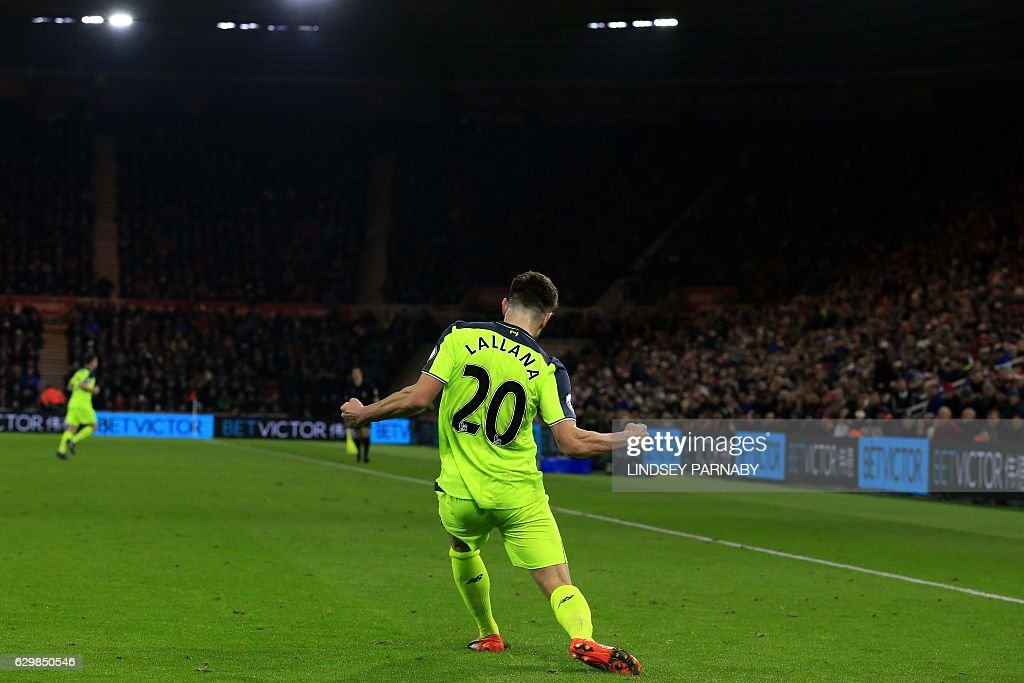 Liverpool's English midfielder Adam Lallana celebrates scoring his team's third goal during the English Premier League football match between Middlesbrough and Liverpool at Riverside Stadium in Middlesbrough, northeast England on December 14, 2016. / AFP / Lindsey PARNABY / RESTRICTED TO EDITORIAL USE. No use with unauthorized audio, video, data, fixture lists, club/league logos or 'live' services. Online in-match use limited to 75 images, no video emulation. No use in betting, games or single club/league/player publications. /