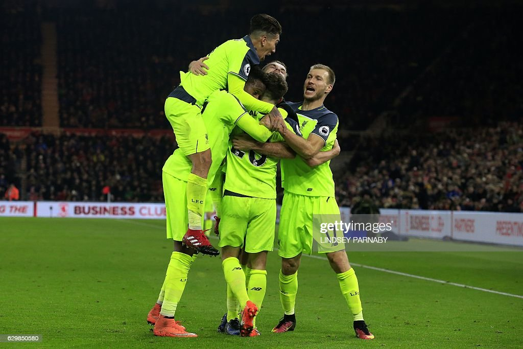 Liverpool's English midfielder Adam Lallana celebrates scoring his team's third goal with Liverpool's Brazilian midfielder Roberto Firmino (L) and Liverpool's Estonian defender Ragnar Klavan (R) during the English Premier League football match between Middlesbrough and Liverpool at Riverside Stadium in Middlesbrough, northeast England on December 14, 2016. / AFP / Lindsey PARNABY / RESTRICTED TO EDITORIAL USE. No use with unauthorized audio, video, data, fixture lists, club/league logos or 'live' services. Online in-match use limited to 75 images, no video emulation. No use in betting, games or single club/league/player publications. /