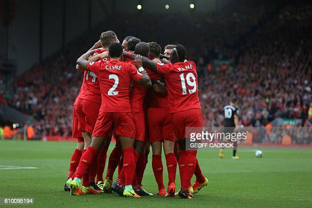 Liverpool's English midfielder Adam Lallana is mobbed by teammates after scoring his team's first goal during the English Premier League football...