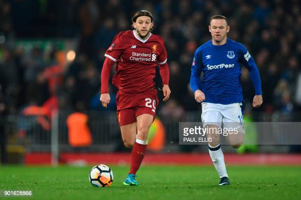 Liverpool's English midfielder Adam Lallana runs away from Everton's English striker Wayne Rooney during the English FA Cup third round football...