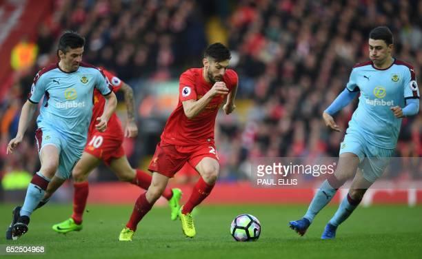 Liverpool's English midfielder Adam Lallana runs between Burnley's English midfielder Joey Barton and Burnley's English defender Matthew Lowton...
