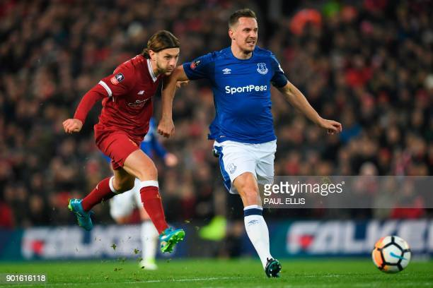 Liverpool's English midfielder Adam Lallana shoots but misses the target under pressure from Everton's English defender Phil Jagielka during the...