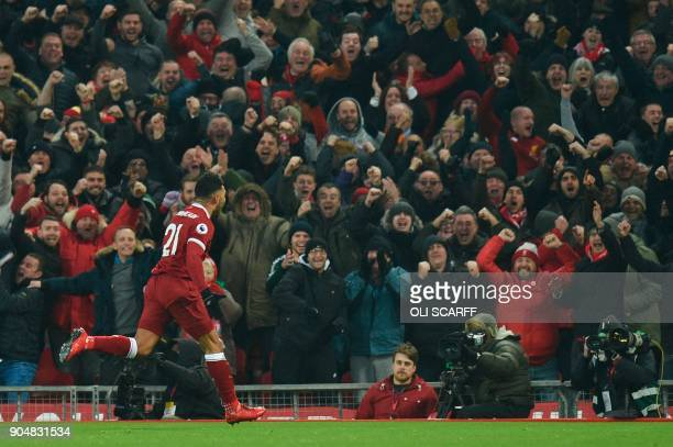 Liverpool's English midfielder Alex OxladeChamberlain celebrates scoring the opening goal during the English Premier League football match between...