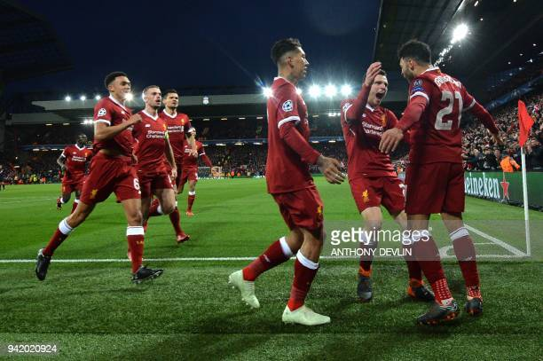 TOPSHOT Liverpool's English midfielder Alex OxladeChamberlain celebrates with teammates scoring the team's second goal during the UEFA Champions...