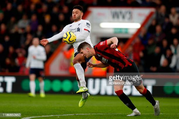 Liverpool's English midfielder Alex OxladeChamberlain goes for a high ball against Bournemouth's Welsh defender Chris Mepham during the English...
