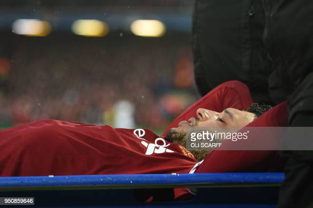 Liverpool's English midfielder Alex OxladeChamberlain is stretchered off the pitch during the UEFA Champions League first leg semifinal football...