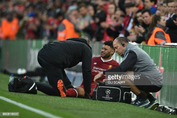 Liverpool's English midfielder Alex OxladeChamberlain picks up an injury during the UEFA Champions League first leg semifinal football match between...