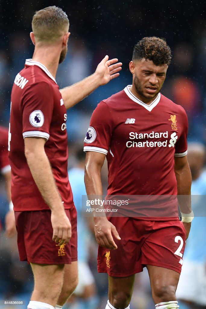 Liverpool's English midfielder Alex Oxlade-Chamberlain (R) reacts with Liverpool's English midfielder Jordan Henderson at the final whistle in the English Premier League football match between Manchester City and Liverpool at the Etihad Stadium in Manchester, north west England, on September 9, 2017. Manchester City won the game 5-0. / AFP PHOTO / Oli SCARFF / RESTRICTED TO EDITORIAL USE. No use with unauthorized audio, video, data, fixture lists, club/league logos or 'live' services. Online in-match use limited to 75 images, no video emulation. No use in betting, games or single club/league/player publications. /