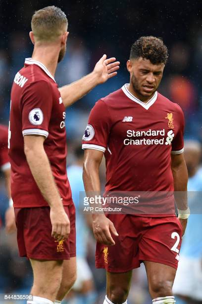 Liverpool's English midfielder Alex OxladeChamberlain reacts with Liverpool's English midfielder Jordan Henderson at the final whistle in the English...