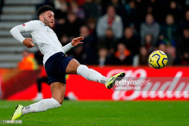 Liverpool's English midfielder Alex Oxlade-Chamberlain strikes the ball to score the opening goal during the English Premier League football match...