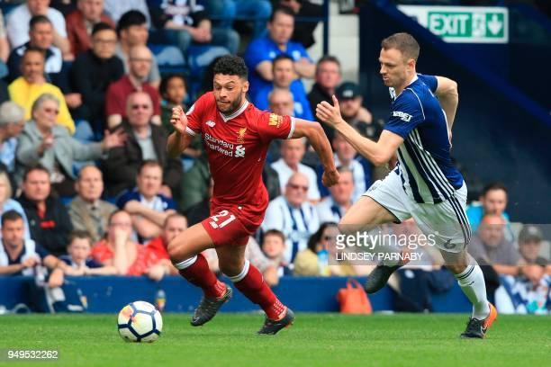 Liverpool's English midfielder Alex OxladeChamberlain takes on West Bromwich Albion's Northern Irish defender Jonny Evans during the English Premier...