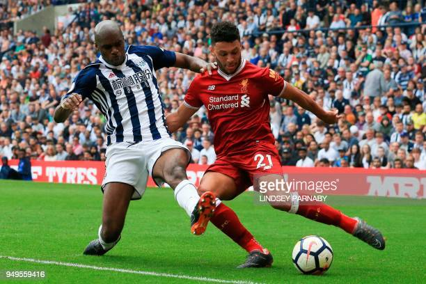 Liverpool's English midfielder Alex OxladeChamberlain tries to cross as West Bromwich Albion's Frenchborn Cameroonian defender Allan Nyom tries to...