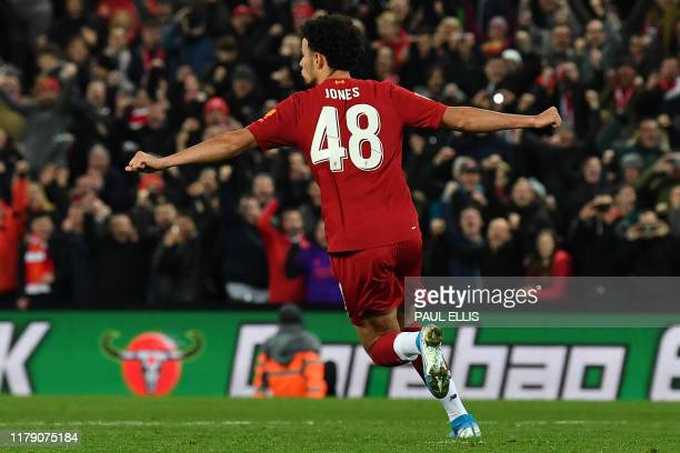 Liverpool's English midfielder Curtis Jones celebrates after scoring the winning penalty in a penalty shoot-out during the English League Cup fourth...
