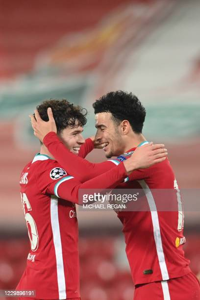 Liverpool's English midfielder Curtis Jones celebrates with Liverpool's Welsh midfielder Neco Williams after he scores his team's first goal during...
