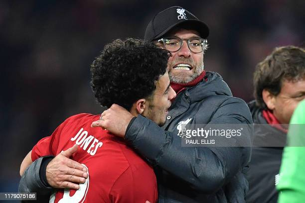 Liverpool's English midfielder Curtis Jones is congratulated by Liverpool's German manager Jurgen Klopp after scoring the winning penalty in a...