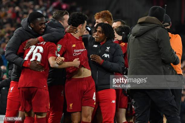 TOPSHOT Liverpool's English midfielder Curtis Jones is mobbed by teammates after scoring the winning penalty after a penalty shootout during the...