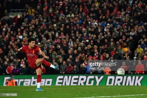 Liverpool's English midfielder Curtis Jones scores the winning penalty in a penalty shootout during the English League Cup fourth round football...