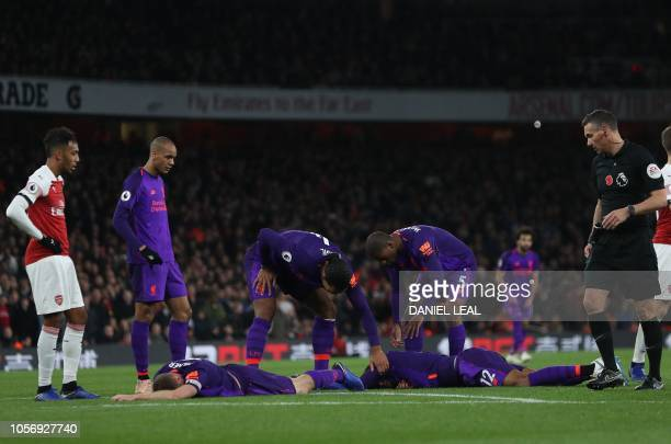 Liverpool's English midfielder James Milner and Liverpool's English defender Joe Gomez lie injured on the ground during the English Premier League...