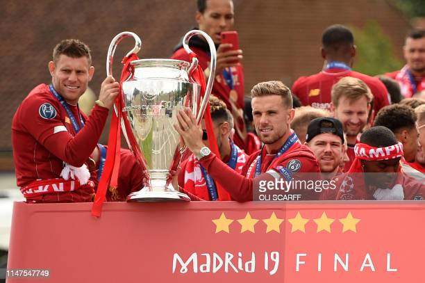 Liverpool's English midfielder James Milner and Liverpool's English midfielder Jordan Henderson hold the European Champion Clubs' Cup trophy during...
