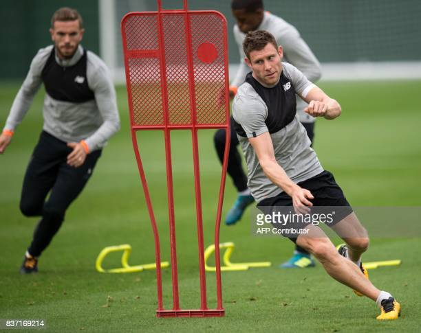 Liverpool's English midfielder James Milner and Liverpool's English midfielder Jordan Henderson attend a team training session at their Melwood...
