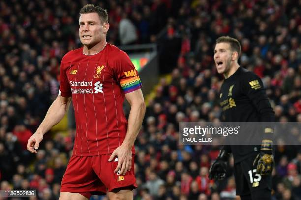 Liverpool's English midfielder James Milner and Liverpool's Spanish goalkeeper Adrian react during the English Premier League football match between...