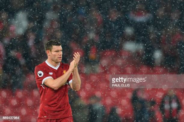 Liverpool's English midfielder James Milner applauds at the end of the English Premier League football match between Liverpool and Everton at Anfield...
