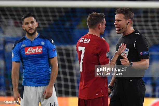 Liverpool's English midfielder James Milner argues with German referee Felix Brych as Napoli's Greek defender Konstantinos Manolas looks on during...