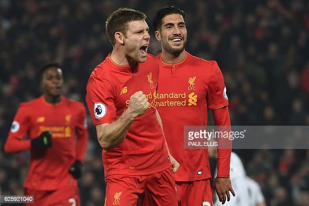 Liverpool's English midfielder James Milner celebrates after scoring their second goal from the penalty spot with Liverpool's German midfielder Emre...