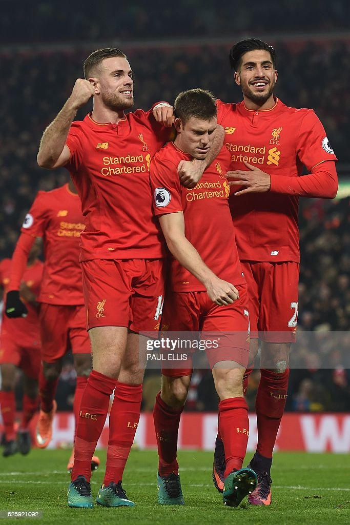 Liverpool's English midfielder James Milner (C) celebrates after scoring their second goal from the penalty spot with Liverpool's English midfielder Jordan Henderson (L) and Liverpool's German midfielder Emre Can (R) during the English Premier League football match between Liverpool and Sunderland at Anfield in Liverpool, north west England on November 26, 2016. / AFP / Paul ELLIS / RESTRICTED TO EDITORIAL USE. No use with unauthorized audio, video, data, fixture lists, club/league logos or 'live' services. Online in-match use limited to 75 images, no video emulation. No use in betting, games or single club/league/player publications. /