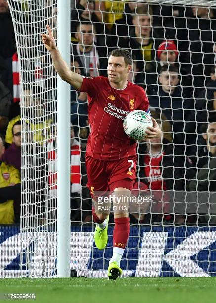 Liverpool's English midfielder James Milner celebrates scoring his team's second goal from the penalty spot during the English League Cup fourth...