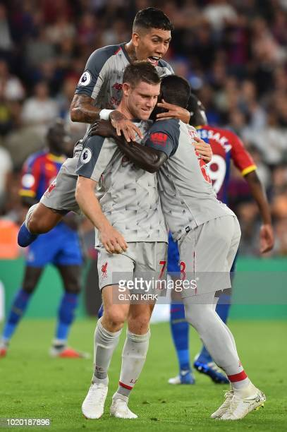 Liverpool's English midfielder James Milner celebrates scoring the opening goal from the penalty spot with Liverpool's Brazilian midfielder Roberto...