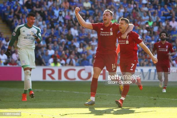 Liverpool's English midfielder James Milner celebrates scoring their second goal from the penalty spot with Liverpool's English midfielder Jordan...