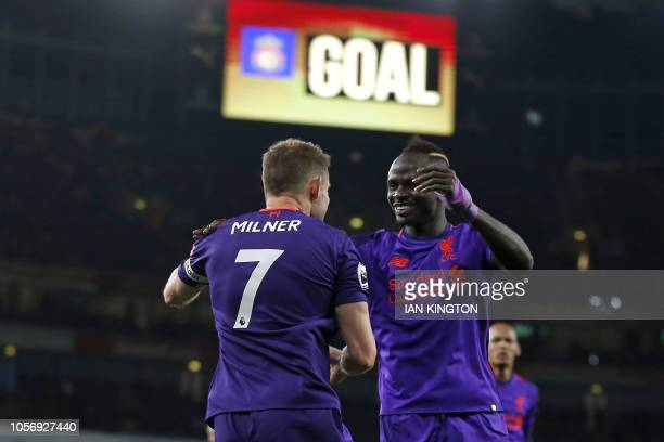 Liverpool's English midfielder James Milner celebrates with Liverpool's Senegalese striker Sadio Mane after scoring the opening goal of the English...