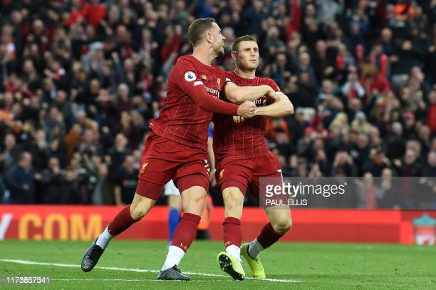 Liverpool's English midfielder James Milner celebrates with Liverpool's English midfielder Jordan Henderson after taking a penalty and scoring his...