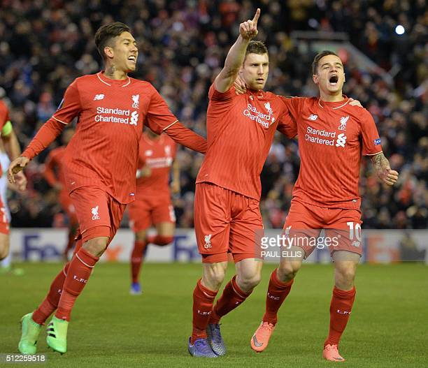 Liverpool's English midfielder James Milner celebrates with Liverpool's Brazilian midfielder Roberto Firmino and Liverpool's Brazilian midfielder...