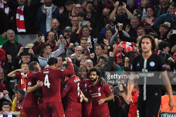 TOPSHOT Liverpool's English midfielder James Milner celebrates with teammates after scoring a penalty during the UEFA Champions League group C...