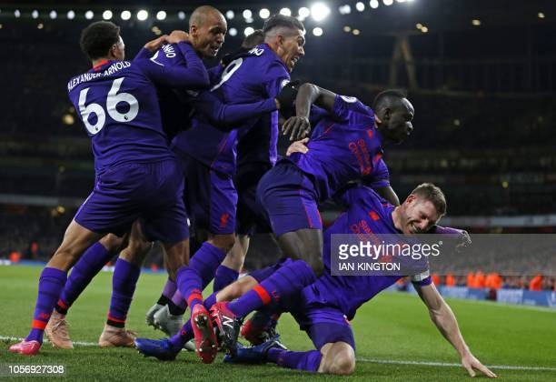 Liverpool's English midfielder James Milner celebrates with teammates after scoring the opening goal of the English Premier League football match...