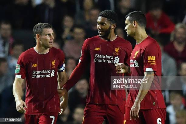 Liverpool's English midfielder James Milner celebrates with teammates after scoring his team's first goal during the English League Cup third round...