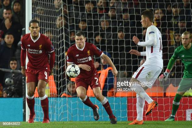 Liverpool's English midfielder James Milner concedes a penalty with a hand ball during the UEFA Champions League first leg semifinal football match...