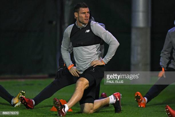 Liverpool's English midfielder James Milner does stretching exercises during a team training session under the floodlights at their Melwood training...