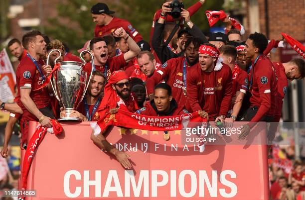 Liverpool's English midfielder James Milner holds the European Champion Clubs' Cup trophy as he stands with teammates Liverpool's English midfielder...