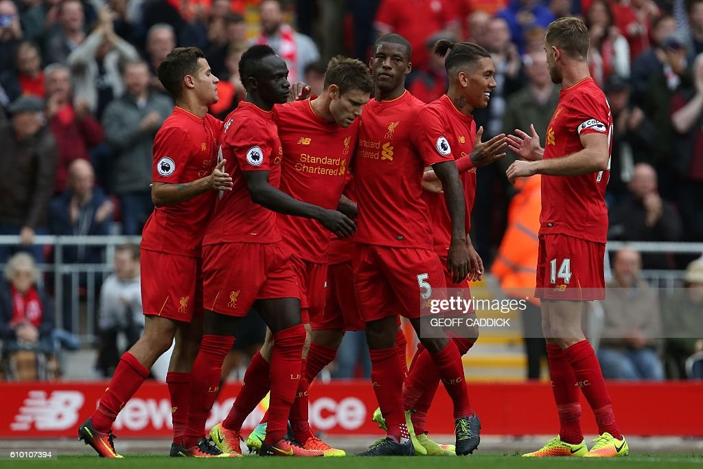 Liverpool's English midfielder James Milner is congrateulated by teammates after shooting from the penalty spot to score his team's fifth goal during the English Premier League football match between Liverpool and Hull City at Anfield in Liverpool, north west England on September 24, 2016. / AFP / Geoff CADDICK / RESTRICTED TO EDITORIAL USE. No use with unauthorized audio, video, data, fixture lists, club/league logos or 'live' services. Online in-match use limited to 75 images, no video emulation. No use in betting, games or single club/league/player publications. /