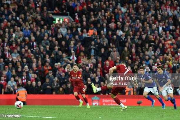 Liverpool's English midfielder James Milner kicks a penalty and scores his team's second goal during the English Premier League football match...
