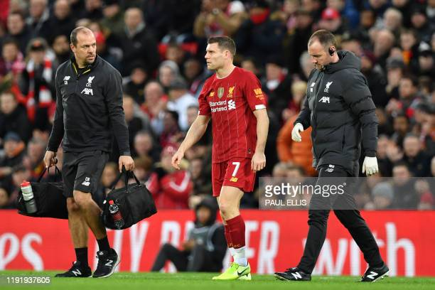 Liverpool's English midfielder James Milner leaves the pitch after being injured during the English FA Cup third round football match between...