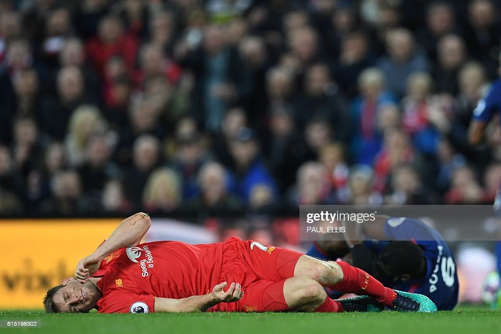 Liverpool's English midfielder James Milner lies injured during the English Premier League football match between Liverpool and Manchester United at Anfield in Liverpool, north west England on October 17, 2016. / AFP / Paul ELLIS / RESTRICTED TO EDITORIAL USE. No use with unauthorized audio, video, data, fixture lists, club/league logos or 'live' services. Online in-match use limited to 75 images, no video emulation. No use in betting, games or single club/league/player publications. /