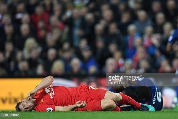 Liverpool's English midfielder James Milner lies injured during the English Premier League football match between Liverpool and Manchester United at...