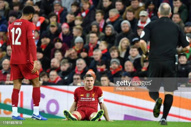Liverpool's English midfielder James Milner lies on the pitch injured during the English FA Cup third round football match between Liverpool and...