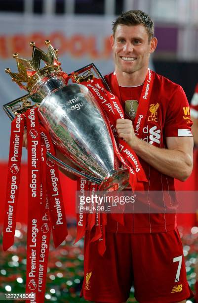 Liverpool's English midfielder James Milner poses with the Premier League trophy during the presentation following the English Premier League...