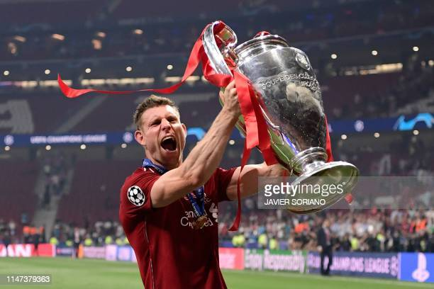 Liverpool's English midfielder James Milner raises the trophy after winning the UEFA Champions League final football match between Liverpool and...