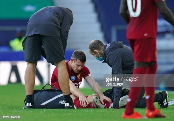 Liverpool's English midfielder James Milner receives treatment after picking up an injury during the English Premier League football match between...